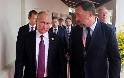 This Nov. 10, 2017, file photo shows Russia's President Vladimir Putin, left, and Russian metals magnate Oleg Deripaska, right, walking to attend the APEC Business Advisory Council dialogue in Danang, Vietnam.  (Mikhail Klimentyev, Sputnik, Kremlin Pool Photo via AP)