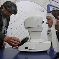 Jorge Cuadros, left, gives a demonstration of a robotic retinal camera to a reporter at the Google I/O conference in Mountain View, California, on May 8, 2018 (AP Photo/Jeff Chiu)