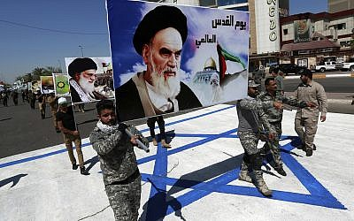 In this June 23, 2017 file photo, supporters of Iraqi Hezbollah brigades, backed by Iran, march on a representation of an Israeli flag with a portrait of late Iranian leader Ayatollah Khomeini and Iran's supreme leader Ayatollah Ali Khamenei, in Baghdad, Iraq. (AP/Hadi Mizban)