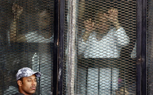 Illustrative: Some of the 739 defendants listen to their verdict from a soundproof glass cage inside a makeshift courtroom in Tora prison in Cairo, Egypt, July 28, 2018. (AP Photo/Amr Nabil)