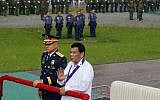 President Rodrigo Duterte gestures to his security not to provide him an umbrella as he reviews the police under a sudden downpour to mark the 117th Philippine National Police Service anniversary at Camp Crame in suburban Quezon city northeast of Manila, Philippines, Aug. 8, 2018.  With him is Philippine Natinal Police Chief Gen. Oscar Albayalde. (AP Photo/Bullit Marquez)