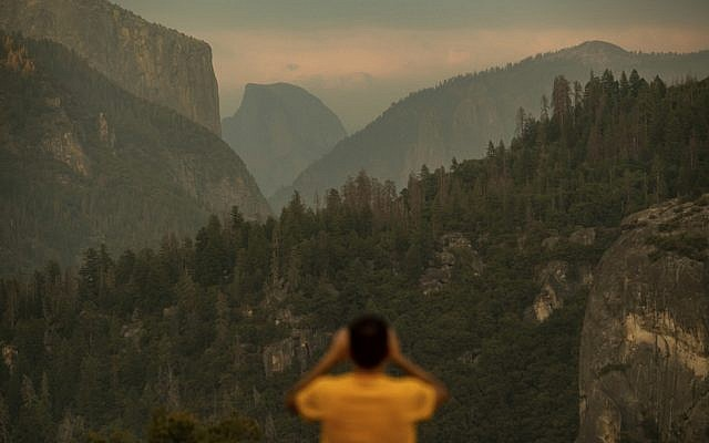 In this July 24, 2018, file photo, Francisco Avendano, visiting from Madrid, Spain, photographs Half Dome as smoke from the Ferguson Fire hangs over Yosemite National Park, Calif. (AP/Noah Berger)