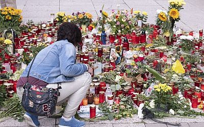 A woman knees in front of candles and flowers at the scene of an altercation in Chemnitz, Germany, August 31, 2018 (AP Photo/Jens Meyer)