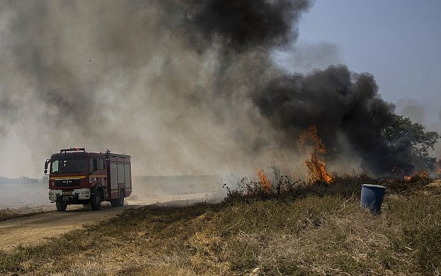 Israeli firefighters arrive to a field set on fire by an incendiary balloon launched by Palestinians from the Gaza Strip, Monday, September 3, 2018 near the Gaza border. (AP Photo/Tsafrir Abayov)