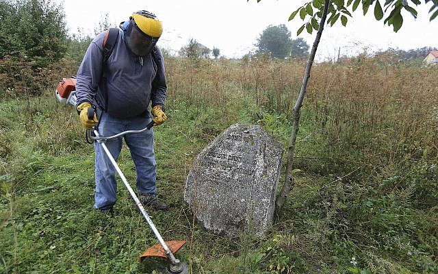 In this photo taken on August 29, 2018, Steven Reece, an ordained Southern Baptist minister who lives near Atlanta cleans an old Jewish cemetery in Rohatyn, the site of a Jewish Heritage project, close to Lviv, Ukraine, Aug. 29, 2018. (AP Photo/Yevheniy Kravs)