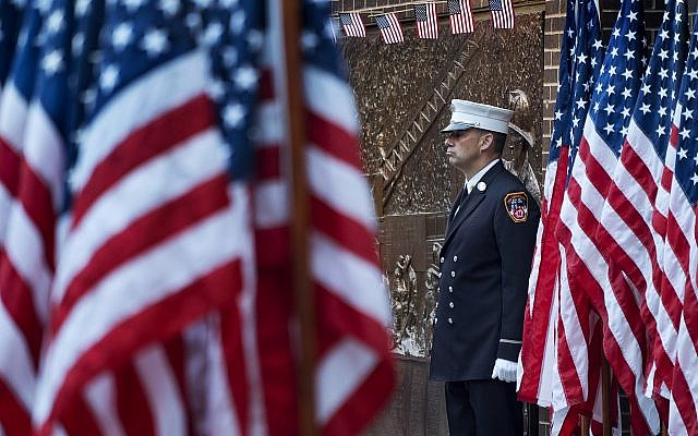 A New York City firefighter stands at attention by a memorial at the side of a firehouse adjacent to One World Trade Center and the 9/11 Memorial site during ceremonies on the anniversary of 9/11 terrorist attacks in New York on Tuesday, Sept. 11, 2018. (AP Photo/Craig Ruttle)