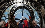 Workers adjust repaired parts of the famed astronomical clock at the Old Town Hall in Prague, Czech Republic, September 11, 2018. (AP Photo/Petr David Josek)