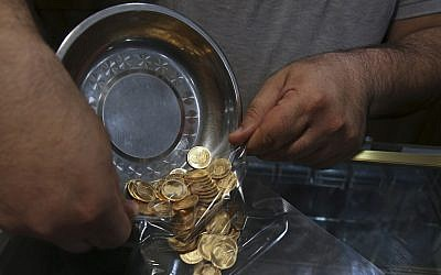 In this Wednesday, Aug. 12, 2018 photo, an Iranian goldsmith counts gold coins in the sprawling Grand Bazaar, that has seen customers eagerly buying gold as a hedge against the falling Iranian rial, in Tehran, Iran. Fear over the economy has brought many to the bazaar in recent days to buy what they can before their savings further dwindle away. (AP Photo/Vahid Salemi)