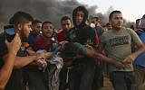 Protesters evacuate a wounded teenager near the fence of the Gaza Strip border with Israel during a protest east of Gaza City, September 14, 2018 (AP Photo/Adel Hana)