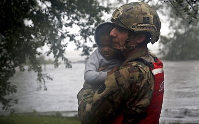 Rescue team member Sgt. Nick Muhar, from the North Carolina National Guard 1/120th battalion, evacuates a young child as the rising floodwaters from Hurricane Florence threatens his home in New Bern, North Carolina, on September 14, 2018. (AP Photo/Chris Seward)