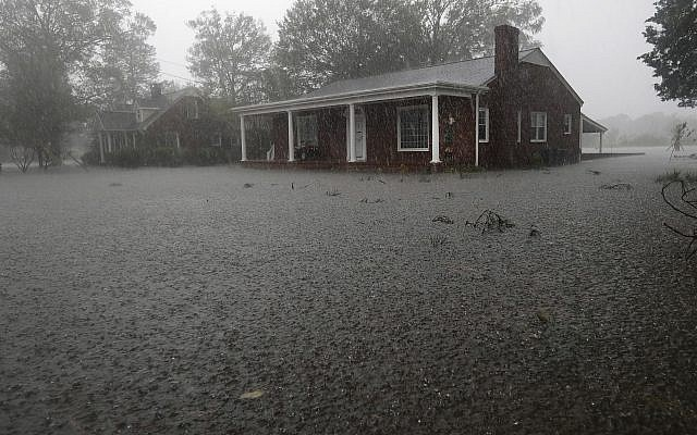 A man makes a phone call from the front porch of his home surrounded bu floodwaters in Jacksonville, North Carolina after Hurricane Florence made landfall Sept. 15, 2018. (AP Photo/Chuck Burton)