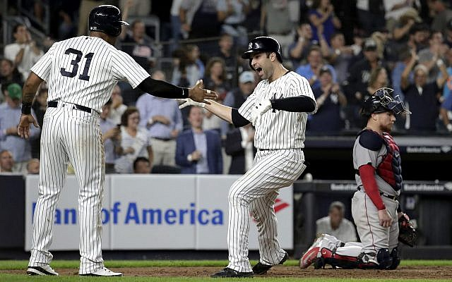 New York Yankees' Neil Walker, right, celebrates with Aaron Hicks (31) after hitting a three-run home run off Boston Red Sox relief pitcher Ryan Brasier during the seventh inning of a baseball game, Sept. 18, 2018, in New York. Red Sox catcher Christian Vazquez is at right. (AP Photo/Julio Cortez)