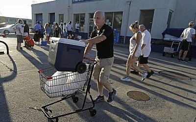 Kyle Crawford uses a shopping cart to carry bags of ice he purchased days after Hurricane Florence in Wilmington, NC, September 19, 2018. (AP Photo/Chuck Burton)