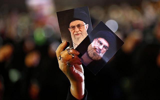 A Hezbollah supporter holds up portraits of Hezbollah leader Sheikh Hassan Nasrallah, right, and Iran's Supreme Leader Ayatollah Ali Khamenei, left, during activities to mark the ninth of Ashura, a 10-day ritual commemorating the death of Imam Hussein, in a southern suburb of Beirut, Lebanon, on September 19, 2018. (AP Photo/Hussein Malla)