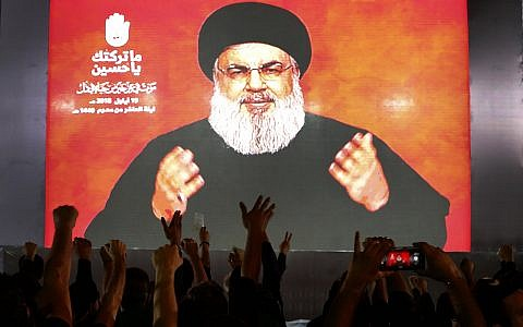 Hezbollah leader Sheik Hassan Nasrallah speaks via a video link, as his supporters raise their hands, during activities to mark the ninth of Ashura, a 10-day ritual commemorating the death of Imam Hussein, in a southern suburb of Beirut, Lebanon, on September 19, 2018. (AP Photo/Hussein Malla)