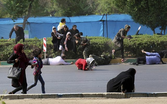 In this photo provided by Mehr News Agency, civilians try to take shelter in a shooting scene, during a military parade marking the 38th anniversary of Iraq's 1980 invasion of Iran, in the southwestern city of Ahvaz, Iran, Sept. 22, 2018 (AP Photo/Mehr News Agency, Mehdi Pedramkhoo)