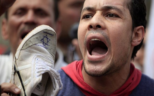 An Egyptian man chants slogans as he hold a shoe with an Israeli flag drawn on it during an anti-Israel protest held after the Friday noon prayer at Al-Azhar mosque in Cairo, Egypt, Friday, May 10, 2013. (AP/Khalil Hamra)