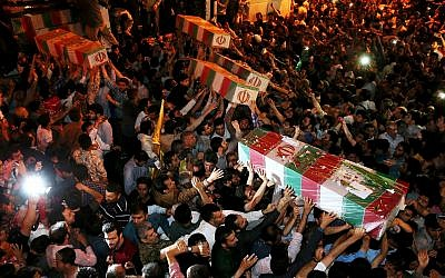 Illustrative image: Iranian mourners carry flag-draped coffins of soldiers killed during the Iran-Iraq war in the 1980s, in Tehran, Iran, June 16, 2015. (AP Photo/Ebrahim Noroozi)