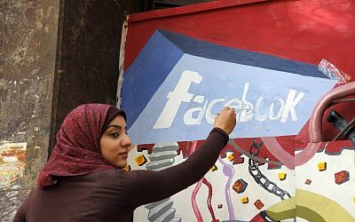 In this March 30, 2011, file photo. an art student from the University of Helwan paints the Facebook logo on a mural commemorating the revolution that overthrew Hosni Mubarak in the Zamalek neighborhood of Cairo, Egypt. (AP/Manoocher Deghati)