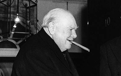 Sir Winston Churchill bites at one of his famous big cigars as he takes leave of prime minister Sir Anthony Eden after lunch at 10 Downing Street in London on Nov. 22, 1955 (AP Photo)