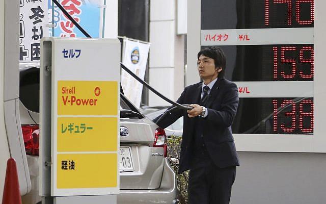 A man puts gas in his car at a Shell filling station in Tokyo Friday, Nov. 28, 2014. (AP/Koji Sasahara)