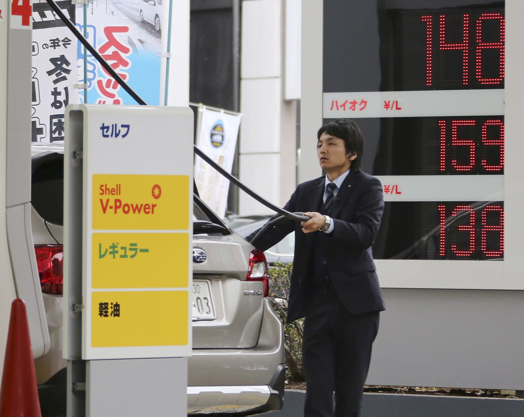 A man puts gas in his car at a Shell filling station in Tokyo Friday Nov. 28 2014