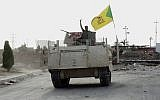In this Wednesday, May 27, 2015 photo, a fighter on an armored vehicle belonging to the Iran-backed Shiite Hezbollah Brigade waves a v-sign as he patrols east of Ramadi, Iraq. (AP)