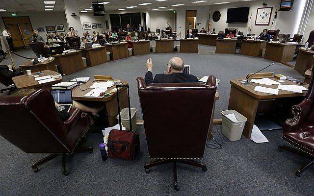 FILE -- State Board of Education member Ken Mercer, center, asks a question as the board listens to testimony during a public hearing on proposed new science textbooks, Sept. 17, 2013, in Austin, Texas (AP Photo/Eric Gay)