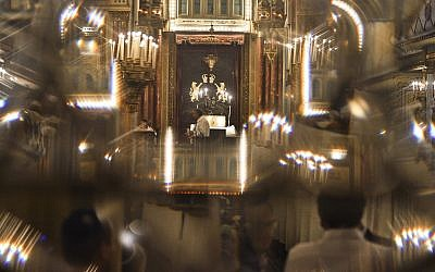 Romanian Jews, seen through a glass door, attend a religious service ahead of the Jewish holiday of Yom Kippur, the Day of Atonement, at the Great Synagogue in Bucharest, Romania, September 13, 2013. (AP Photo/Andreea Alexandru/Mediafax)
