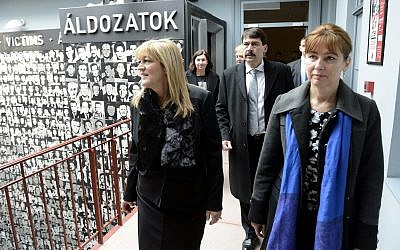 Hungarian President Janos Ader, center, and his wife, Anita Herczegh, right, are escorted by Maria Schmidt, left, as they tour the House of Terror museum to pay tribute on the memorial day for victims of communism in Budapest, Hungary, Wednesday, February 25, 2015. (AP Photo/MTI, Tamas Kovacs)
