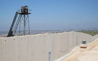 An Israeli construction vehicle drives by a concrete wall being built along the 'Blue Line' separating Israel and Lebanon, as members of the Lebanese Armed Forces watch from a guard tower, near the Israeli town of Rosh Hanikra on September 5, 2018. (Judah Ari Gross/Times of Israel)