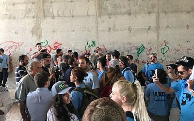 Israeli right-wing activists in blue shirts exchange shouts with Palestinian activists and local residents in a passageway under the Route 1 highway near the West Bank Bedouin village of Khan al-Ahmar, September 7, 2018. (Twitter screen capture)