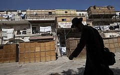 """Illustrative: An ultra-Orthodox Jew walks by a street full of """"Sukkot"""" (temporary dwellings), in the religious neighborhood of Mea Shearim in Jerusalem on October 10, 2016.  (Nati Shohat/ FLASH90)"""