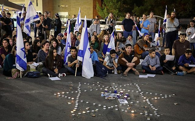 Mourners light candles in memory of Ari Fuld, at the site where he was murdered earlier in the day, at the Gush Etzion Junction, September 16, 2018. (Gershon Elinson/Flash90)