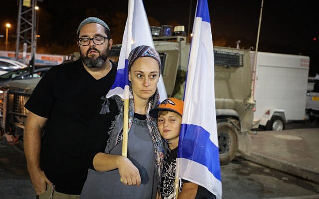 People light candles in memory of Ari Fuld, at the site where he was murdered, at the Gush Etzion Junction, September 16, 2018. (Gershon Elinson/FLASH90)