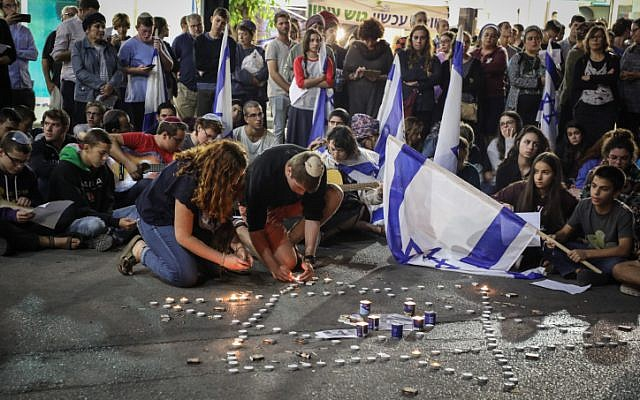 People light candles in memory of Ari Fuld, at the site where he was murdered at the Gush Etzion Junction, September 16, 2018. (Gershon Elinson/FLASH90)
