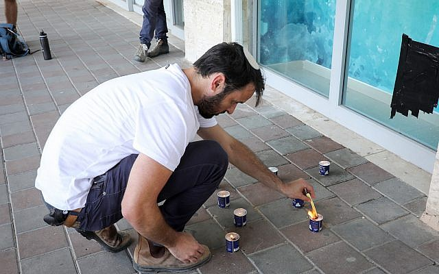 People light candles in memory of Ari Fuld, at the site where he was murdered in a terror attack, at the Gush Etzion Junction, September 16, 2018. (Gershon Elinson/FLASH90)
