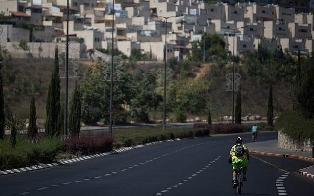 Israelis ride their bicycles along the empty road in Jerusalem on Yom Kippur, September 19, 2018 (Hadas Parush/Flash90)