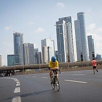 Israelis ride their bicycles along the empty Ayalon highway in Tel Aviv, on Yom Kippur, September 19, 2018 (Miriam Alster/Flash 90)