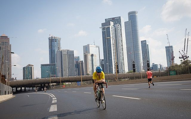 Israelis ride their bicycles along the empty Ayalon highway in Tel Aviv, on Yom Kippur, September 19, 2018 (Miriam Alster/Flash 90)