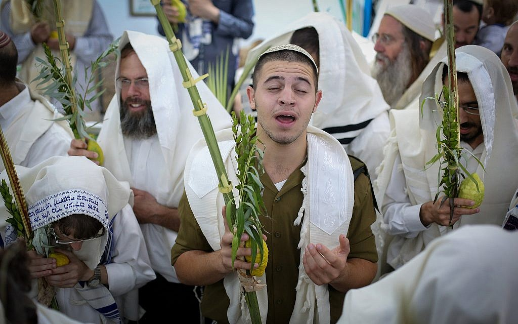 Jewish men wave the four species to mark the holiday of Sukkot during morning prayers at the Abuhav synagogue in the northern Israeli city of Safed on September 25, 2018. (David Cohen/Flash90)