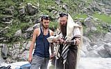 Rabbi Dror Shaul helps a tourist put on phylacteries near his Chabad houses in the Himalayas. (Courtesy)