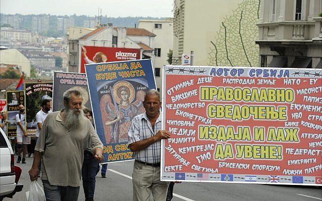 In June 2018, Serb nationalists march along a Belgrade street, carrying banners that protest the desecration of Serbian Orthodox churches and blame the country's economic problems on 'evil foreign influences' such as NATO, the World Bank, reality TV, the EU, Masons, genetically modified food, Israel and the United States. (Larry Luxner/Times of Israel)
