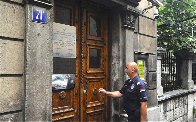 Serbian police officer provides security at the Belgrade headquarters of Serbia's Federation of Jewish Communities, June 2018. (Larry Luxner/Times of Israel)
