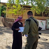 A Civil Administration official hands a notice regarding the pending demolition of Khan al-Ahmar to one of its residents on September 23, 2018. (Civil Administration)
