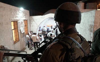 An IDF soldiers looks on as Jewish worshipers arrive at the Joseph's Tomb holy site in the northern West Bank city of Nablus on September 26, 2018. (IDF)