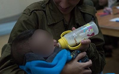 An IDF soldier feeds a Syrian baby as part of the IDF's 'Operation Good Neighbor' project, which helped thousands of Syrians before Israel shut it down after Syrian dictator Bashar Assad took control of the area bordering the Golan Heights. (Israel Defense Forces)