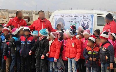 Syrian children show off the coats and winter clothes they received as part of the IDF's 'Operation Good Neighbor' project, which helped thousands of Syrians before Israel shut it down after Syrian dictator Bashar Assad took control of the area bordering the Golan Heights. (Israel Defense Forces)