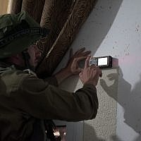 IDF soldiers measure the home of a Palestinian terrorist who stabbed an Israeli man to death in order to prepare the building for demolition in the West Bank village of Yatta, near Hebron, on September 17, 2018. (Israel Defense Forces)