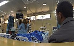 Illustrative: A father waits while hospital staff attend to his baby, brought to Israel for life-saving heart surgery by Shevet Achim NGO. (Screen capture: Vimeo)